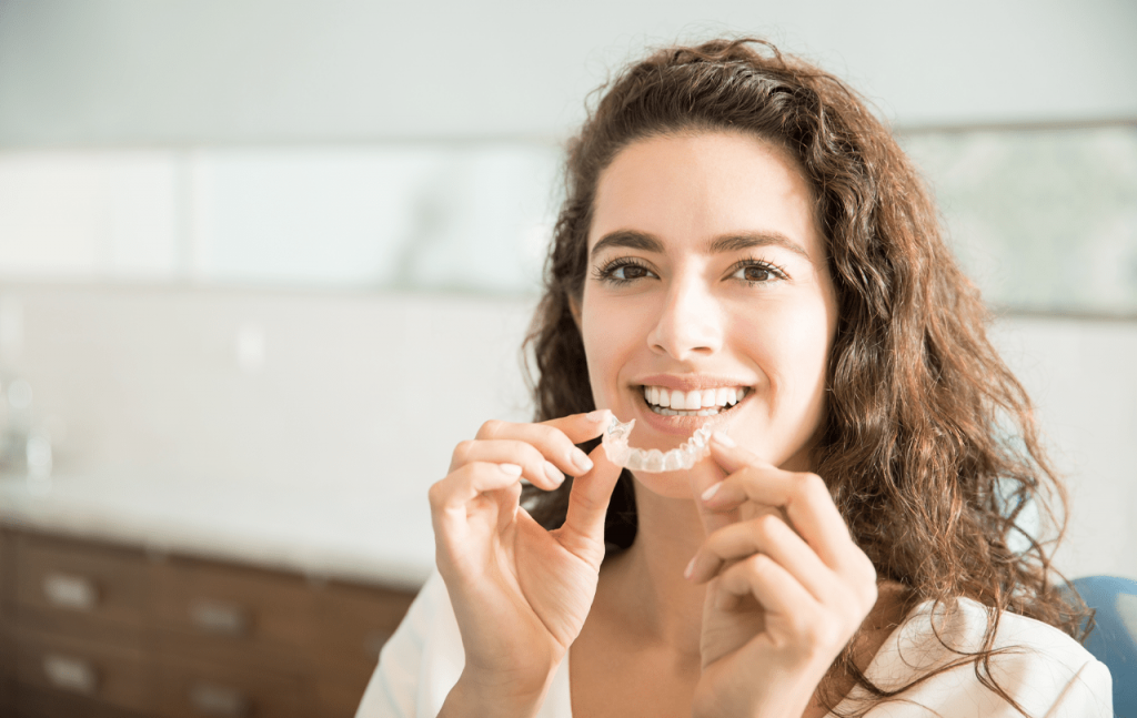 Woman smiles while holding up a set of clear retainers
