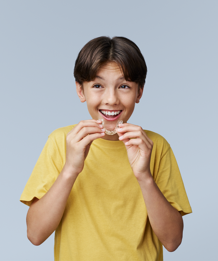 Young boy smiles while holding an Invisalign retainer